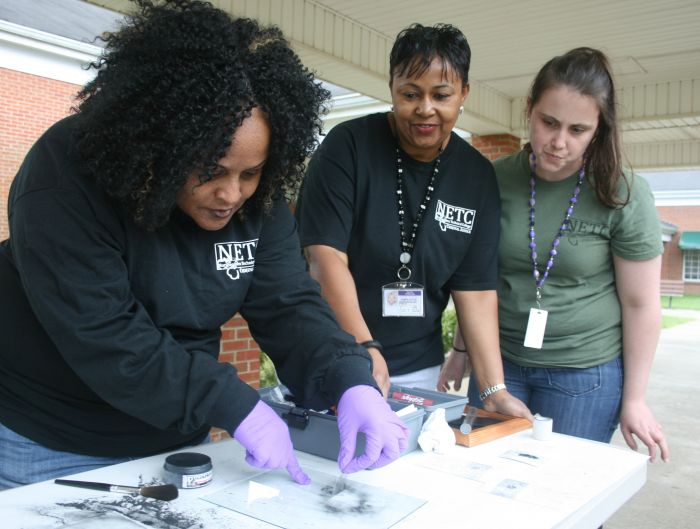 Criminal Justice student Cynthia McCormick (on left) practices her technique for fingerprint dusting during class at Northeastern Technical College.